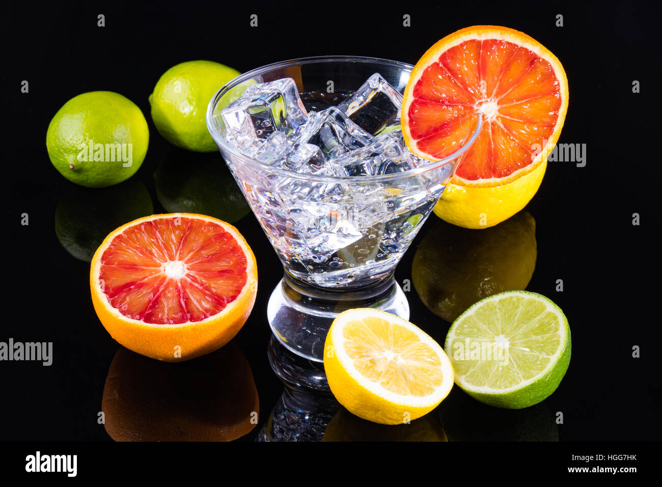 Sparkling beverage in a martini glass with colorful citrus on a black backgorund - Stock Image
