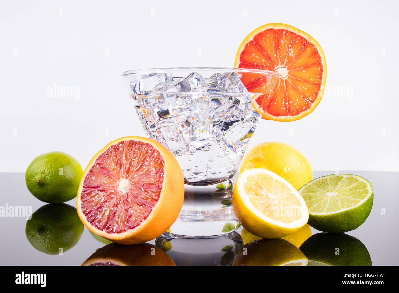 Sparkling beverage in a martini glass with colorful citrus - Stock Image