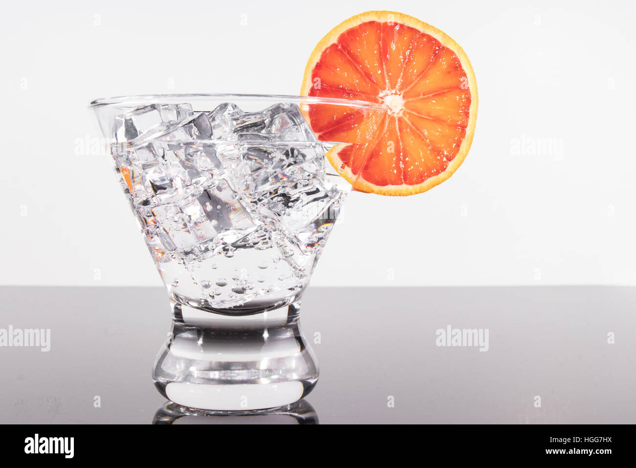 Sparkling beverage in a martini glass with a blood orange slice - Stock Image