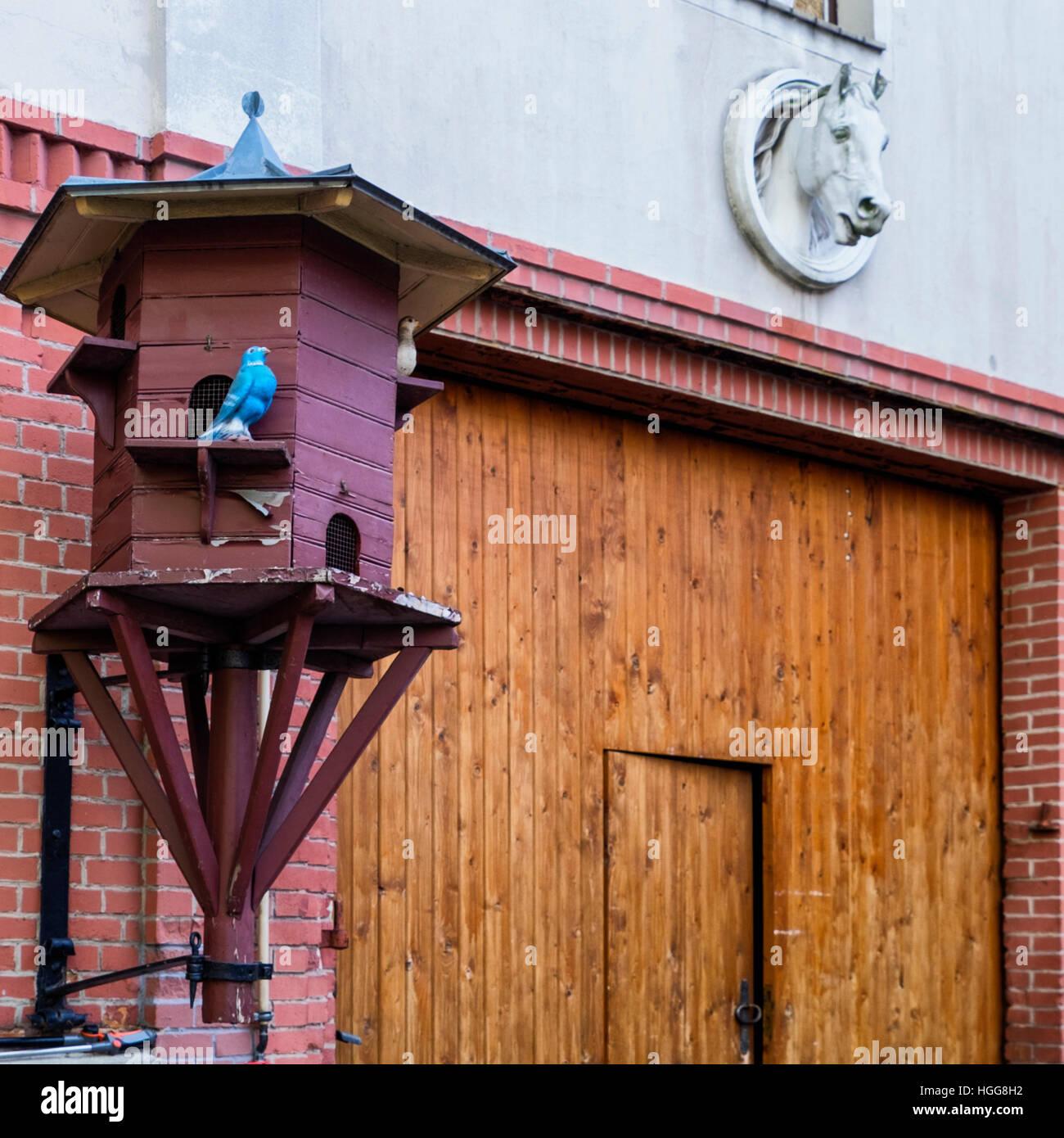 Berlin,Neukölln. Bird nesting box and artificial birds at stables in Rixdorf historic Bohemian Village - Stock Image