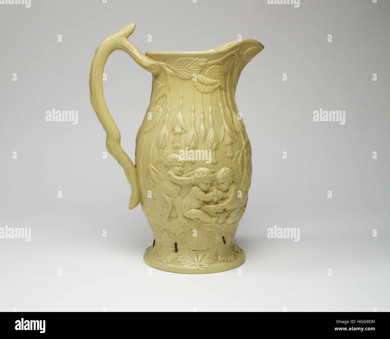 antique English stoneware ewer. Decorated in high relief with Bacchus putti, flowers and leaves. The ewer measures Stock Photo