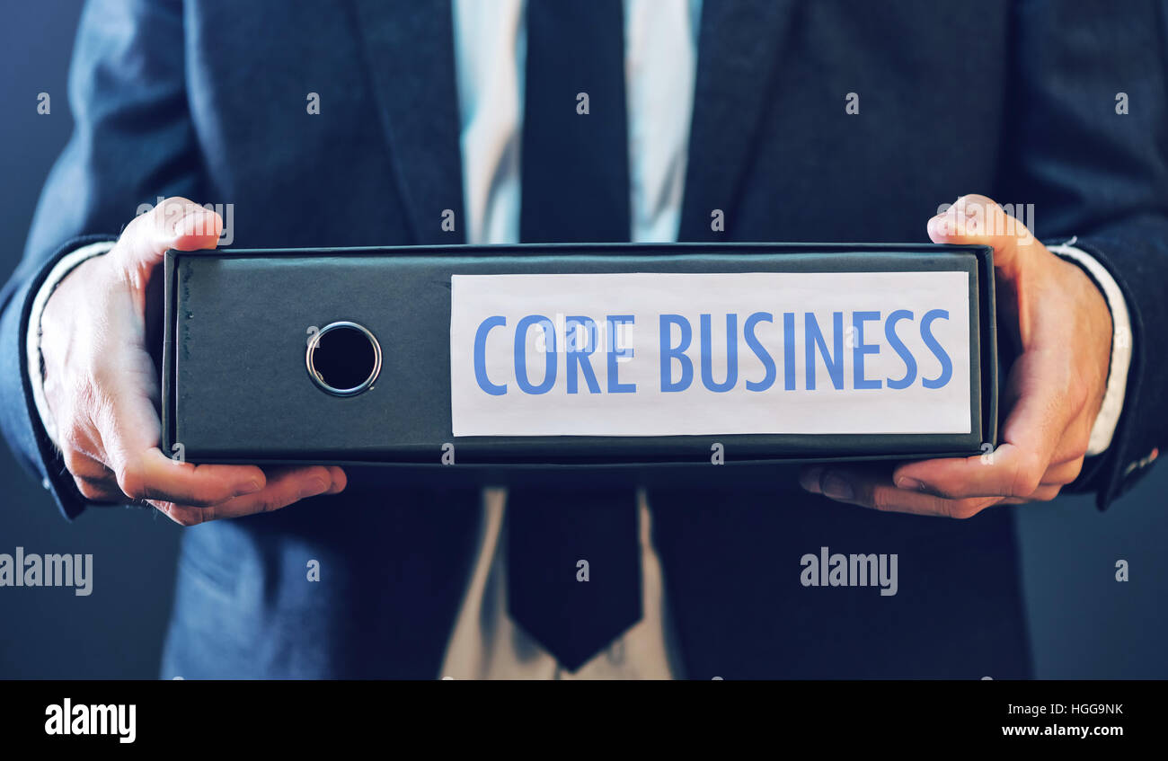 Core business with businessman and document ring binder, primary area or activity that company focuses on in its - Stock Image