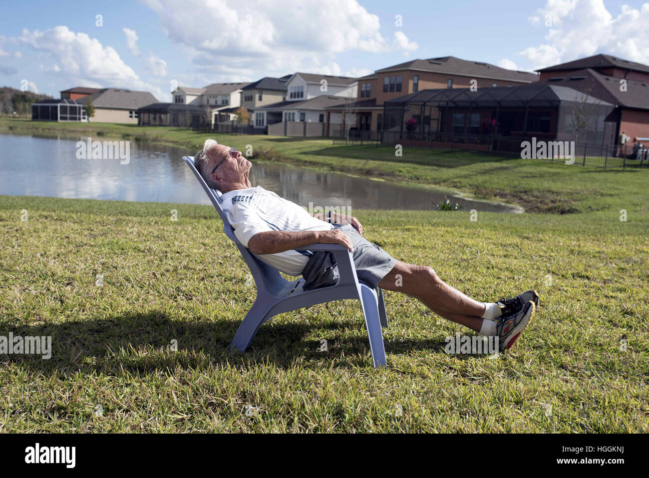 Wesley Chapel, FL, USA. 24th Dec, 2016. Retired executive his 80s relaxes in sunshine outside new home in a suburban - Stock Image