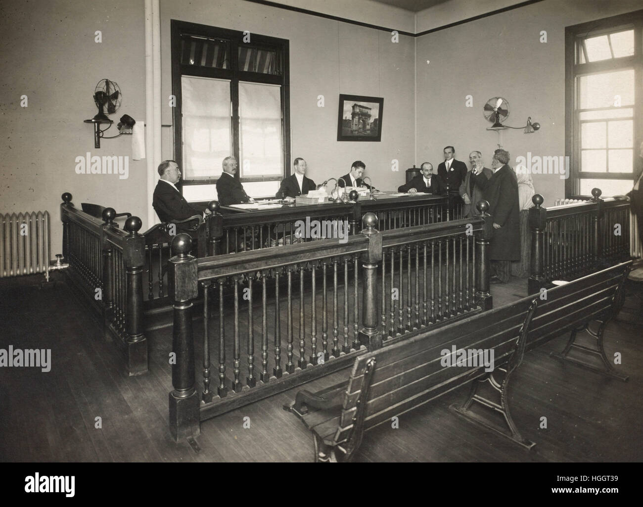 A bearded immigrant appearing before a board of inquiry  - Ellis Island Immigration Station 1902-1913 - Photo : - Stock Image