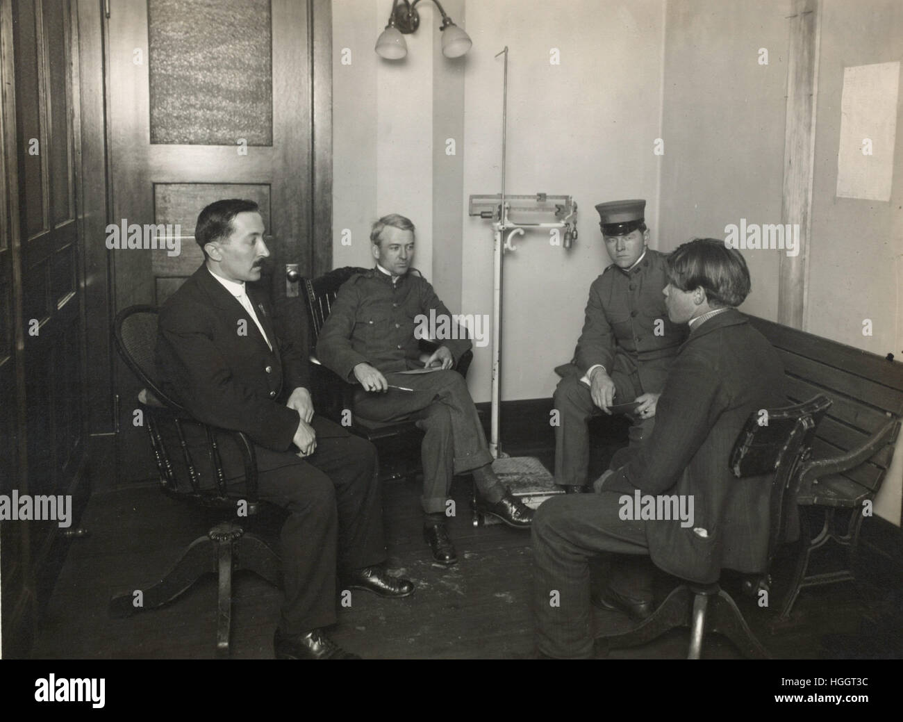 A private interview between a young immigrant and an Ellis Island official  - Ellis Island Immigration Station 1902 - Stock Image
