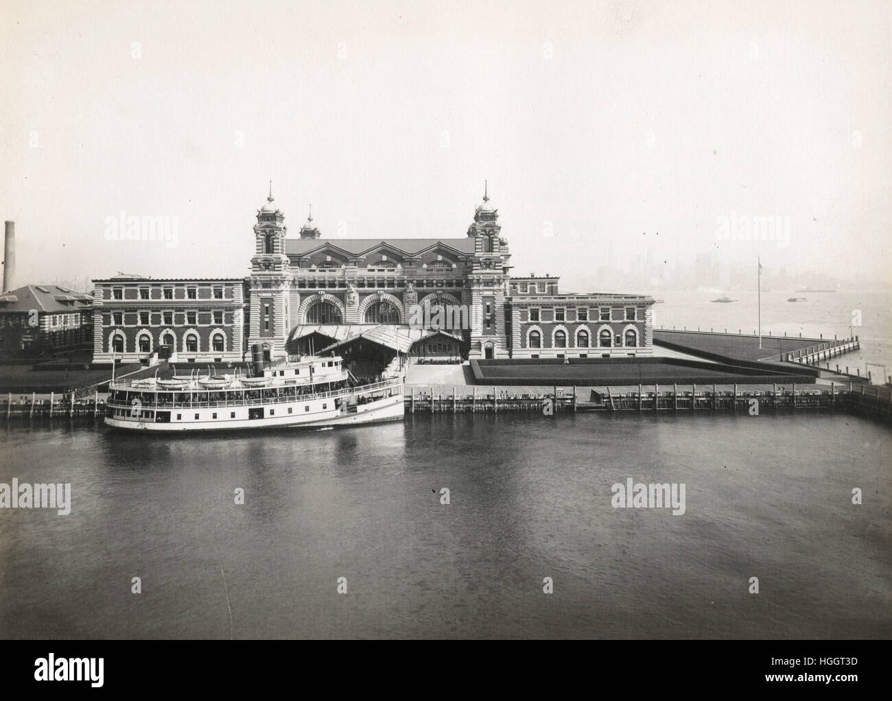 An excellent view of the front facade of the Immigration Station; a boat is docked in front  - Ellis Island Immigration - Stock Image