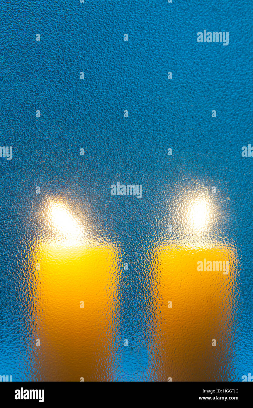 Two lit up candles viewed through a frosted glass. - Stock Image