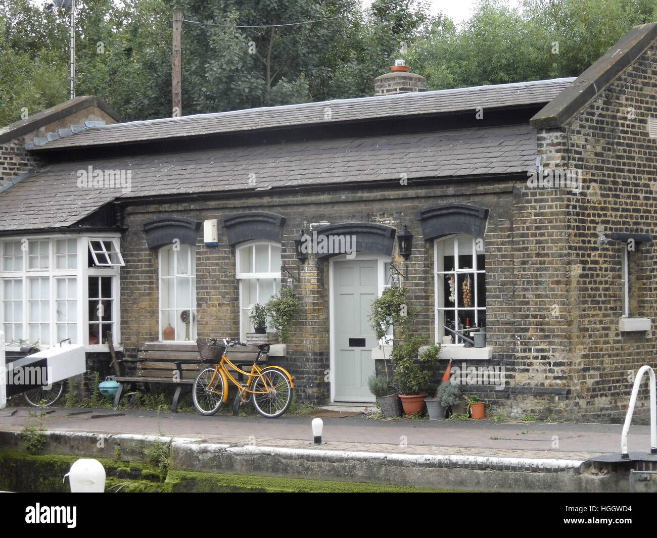 Lock keepers house with yellow cycle parked outside Stock Photo