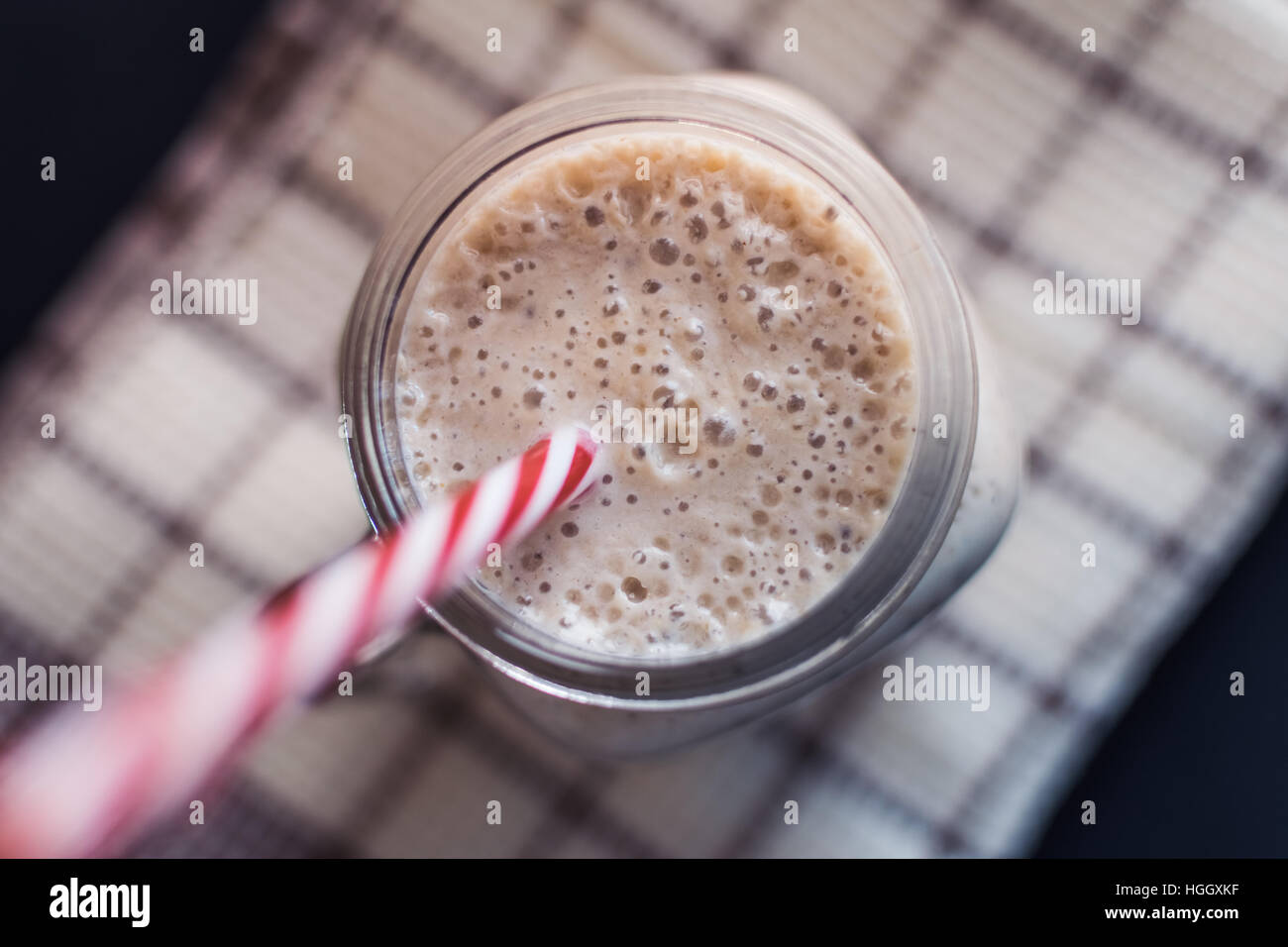Healthy smoothie. Banana,oats,Chia seeds and honey mix. Bananas in background, Top view. - Stock Image