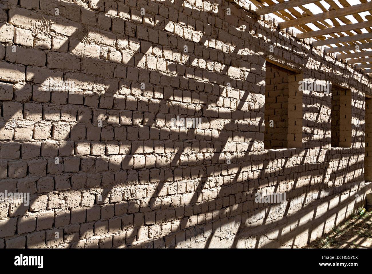 Shadows on a mud brick wall. - Stock Image