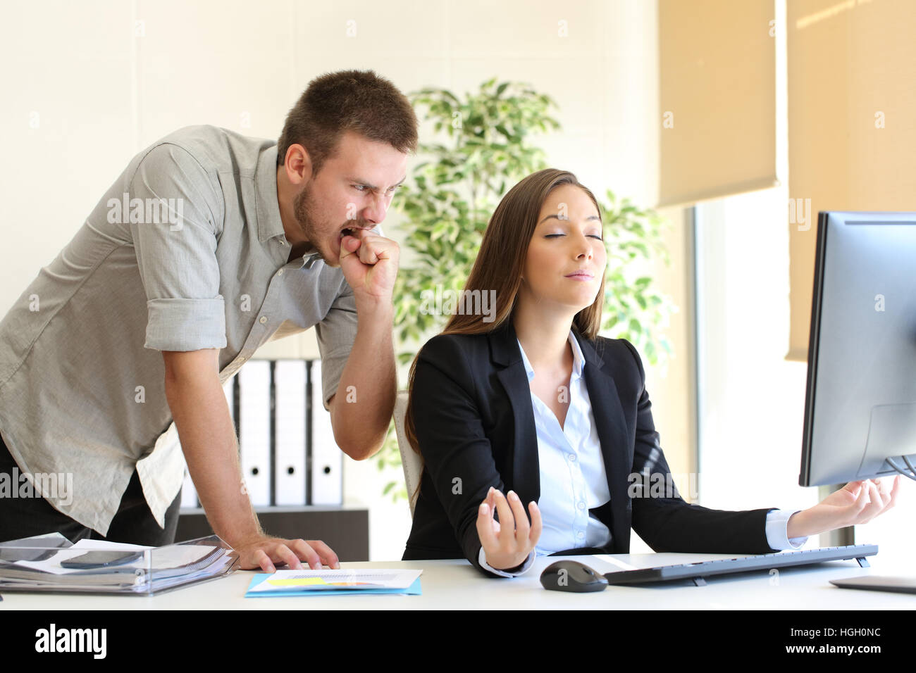 Angry businessman hating to his relaxed colleague at office - Stock Image