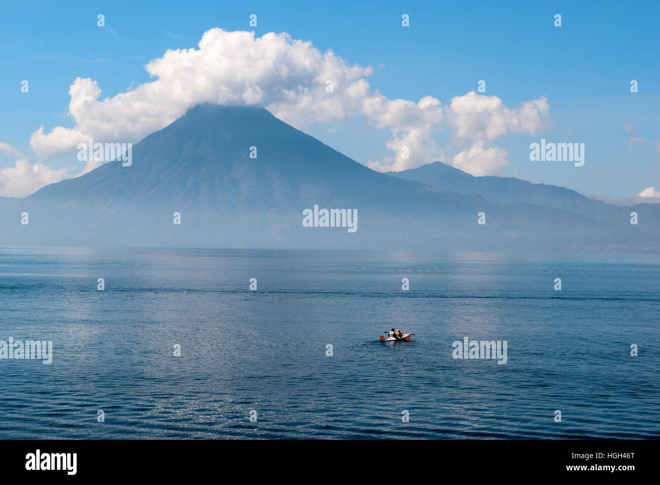 Lonely boat on a beautiful lake with volcano in background - Stock Image
