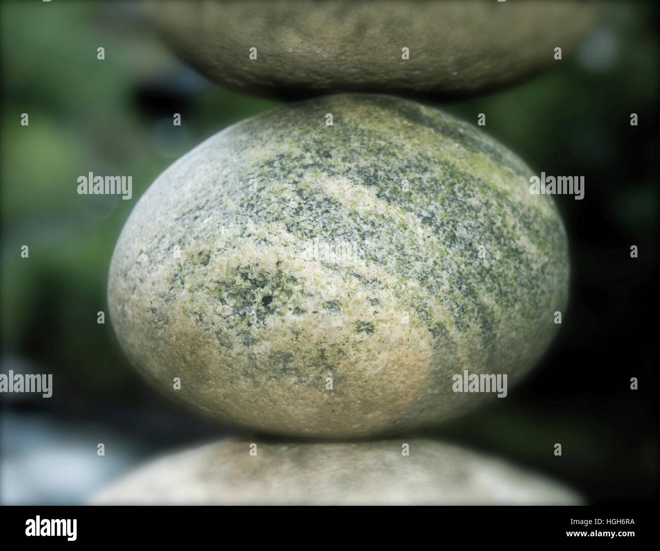 Stuck between a rock and a hard place. River stone suspended between two other stones. Stock Photo