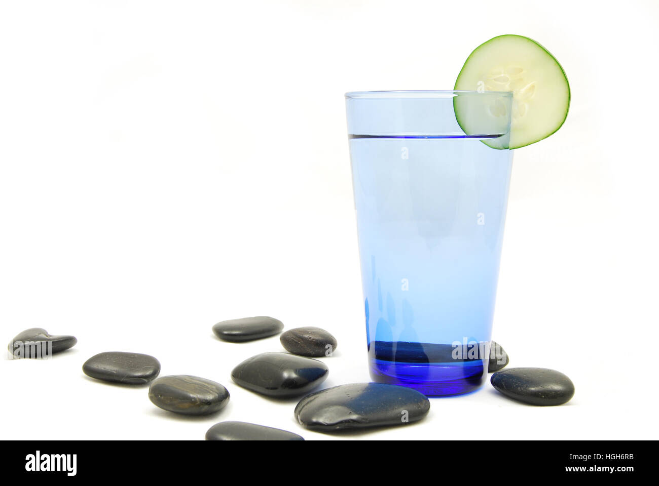 Cucumber water in a spa like zen setting with smooth stones - Stock Image