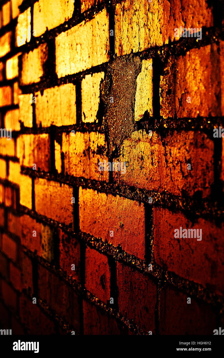 Red brick wall with the setting sun reflecting off of it. - Stock Image