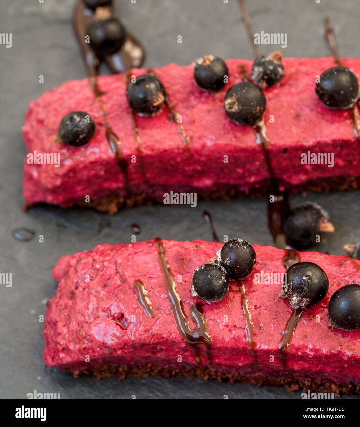 Raw chocolate berry cake with berries and chocolate syrup and currant.  Love for a healthy raw food concept. - Stock Image