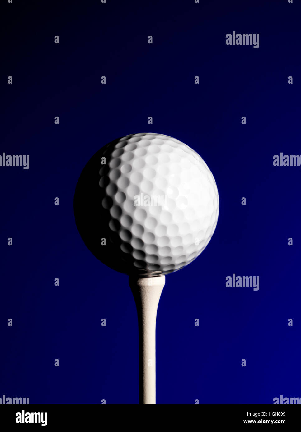 Golf Ball and tee with a blue background - Stock Image