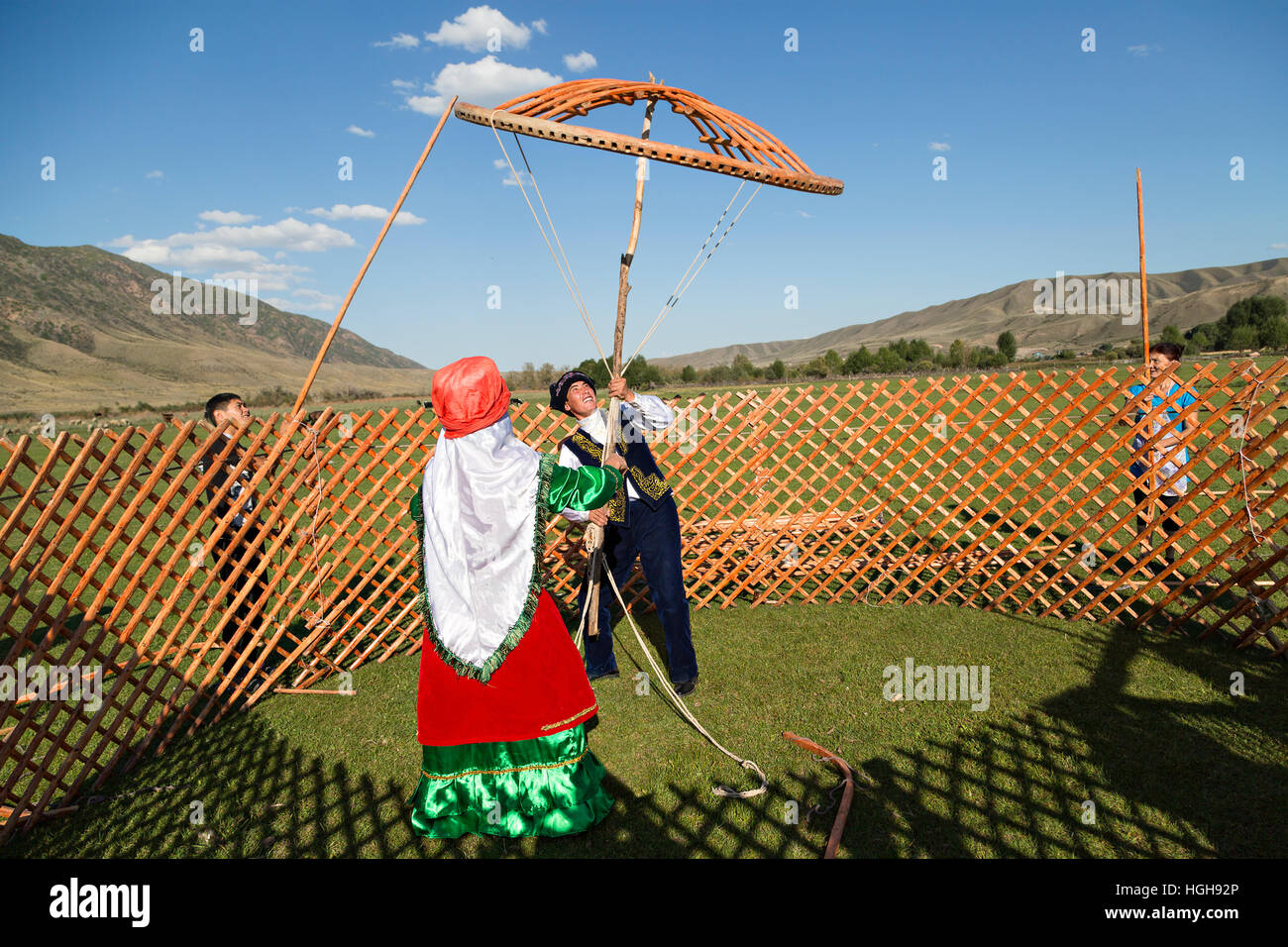 Nomadic people in national costumes building a yurt and holding the crown of the dome of a yurt known as Shangyrak - Stock Image
