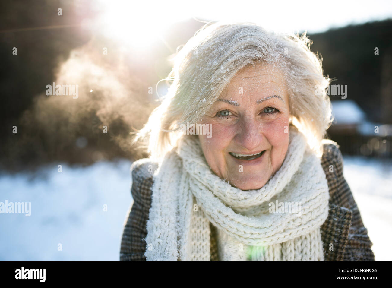 Beautiful senior woman on a walk, covered by snow - Stock Image