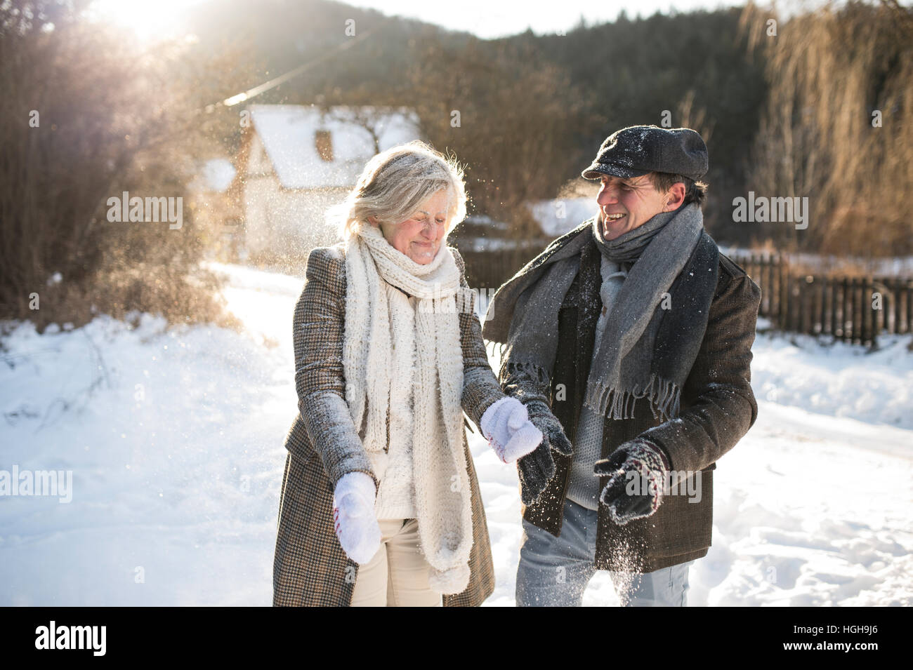 Beautiful senior couple blowing snow in sunny winter nature - Stock Image