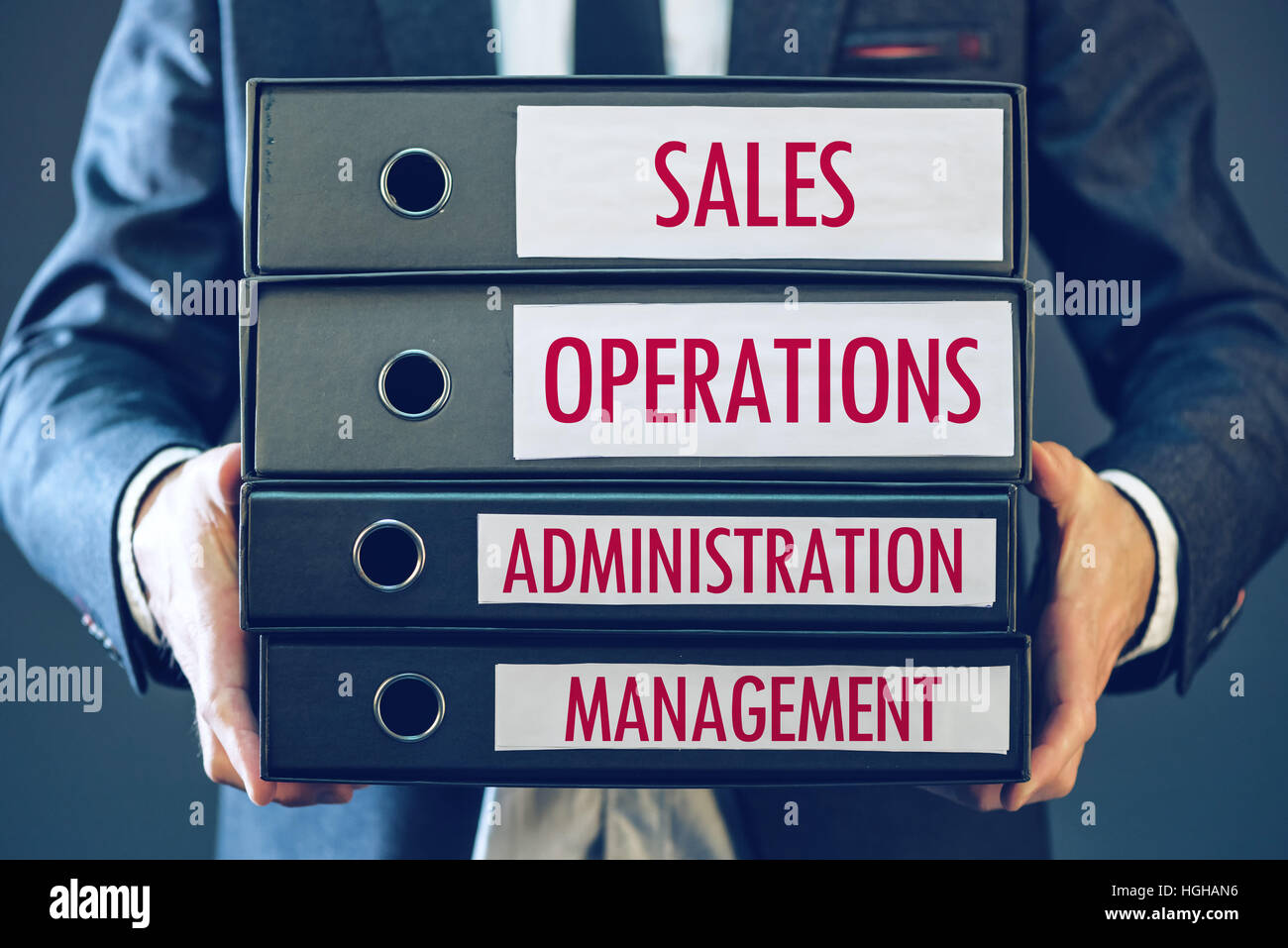 Four core business functions - sales, operations, administration and management with businessman holding ring binders - Stock Image