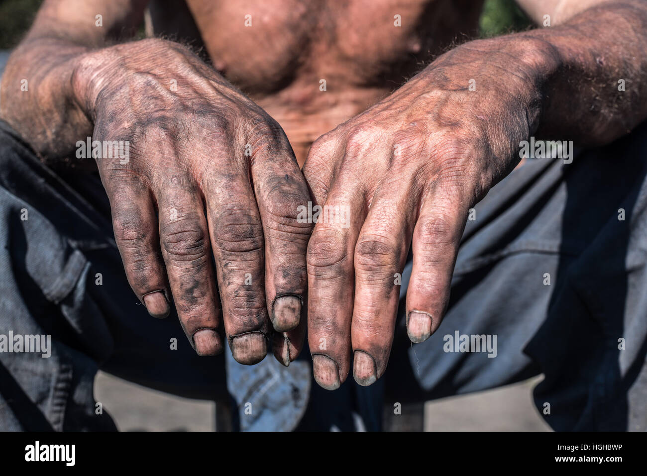 Charcoal-burners worker man with dirty hands. - Stock Image