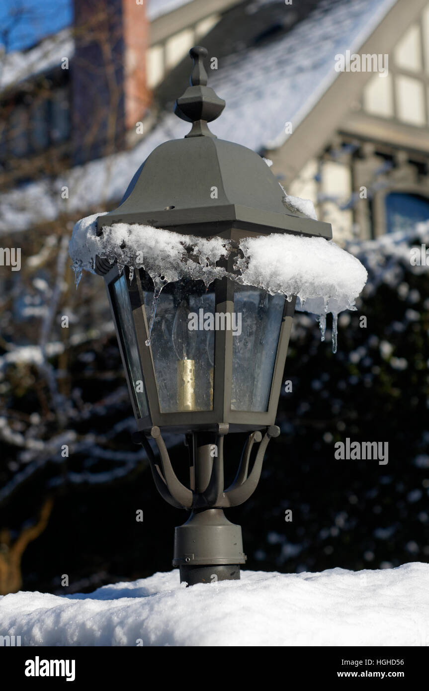 Metal lantern covered in snow and ice with Tudor style house in back, Vancouver, Canada - Stock Image
