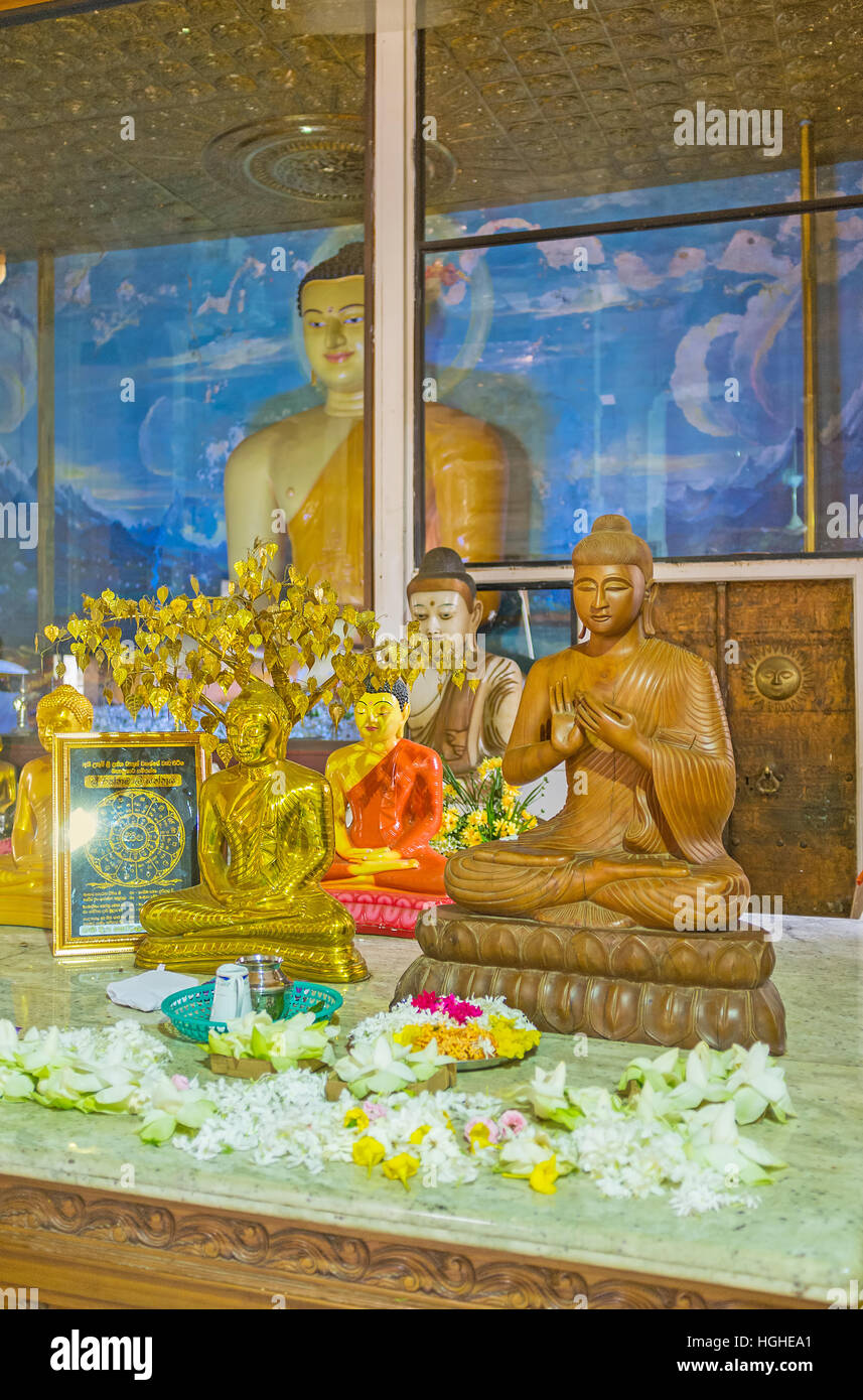 The interior of Image House of Bodhi Tree Temple with statue of Buddha and small sculptures on the altar Stock Photo