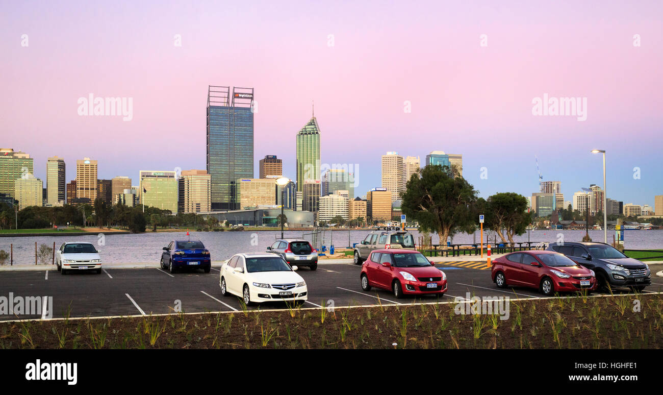 Cars parked in a car park with Perth city in the distance. South Perth, Western Australia - Stock Image