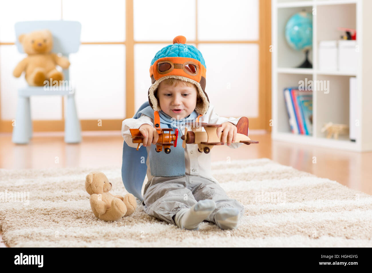 Happy kid boy playing with toy airplane at home in his room - Stock Image