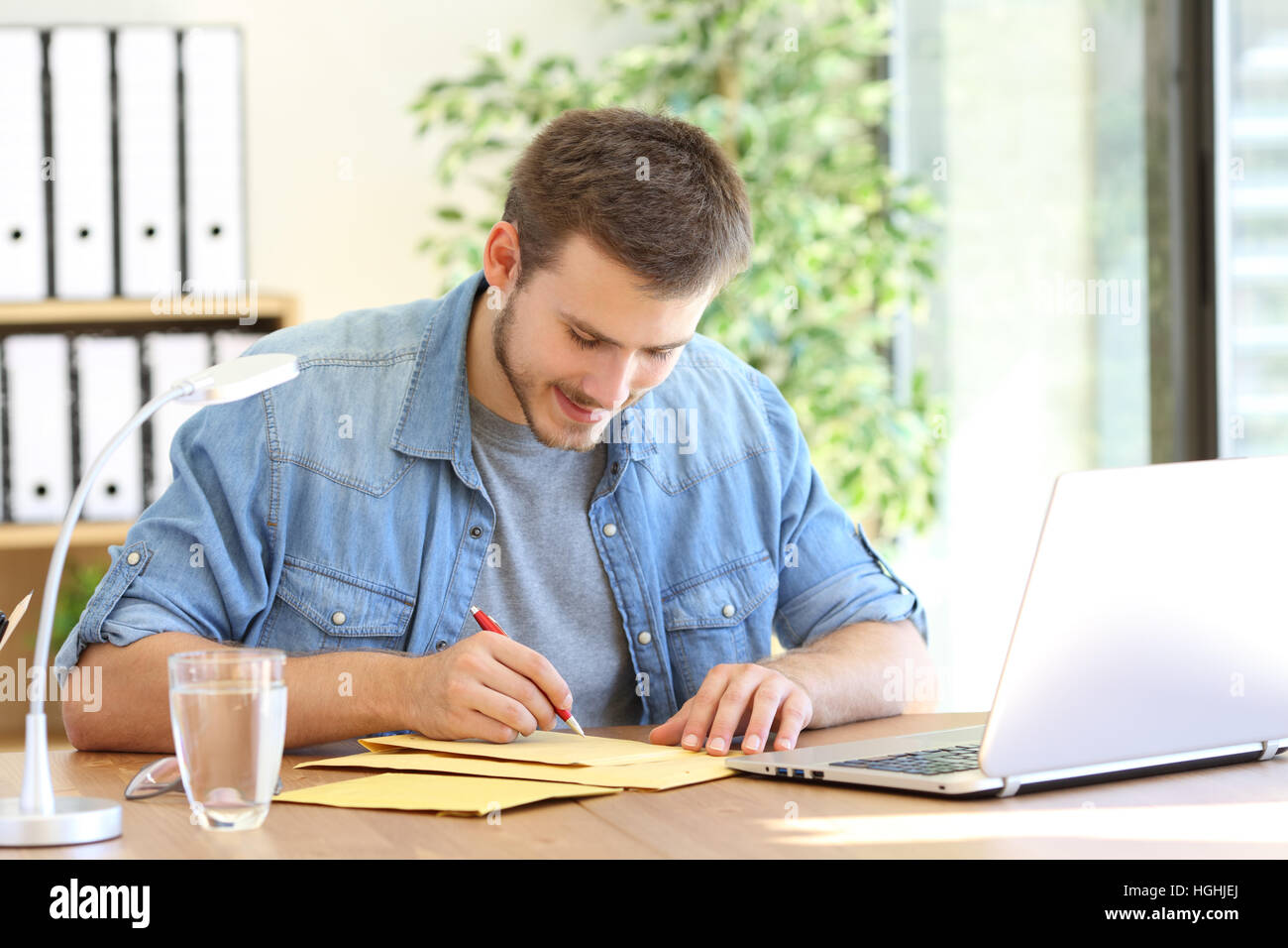 Entrepreneur writing address in a padded envelope before to send it - Stock Image