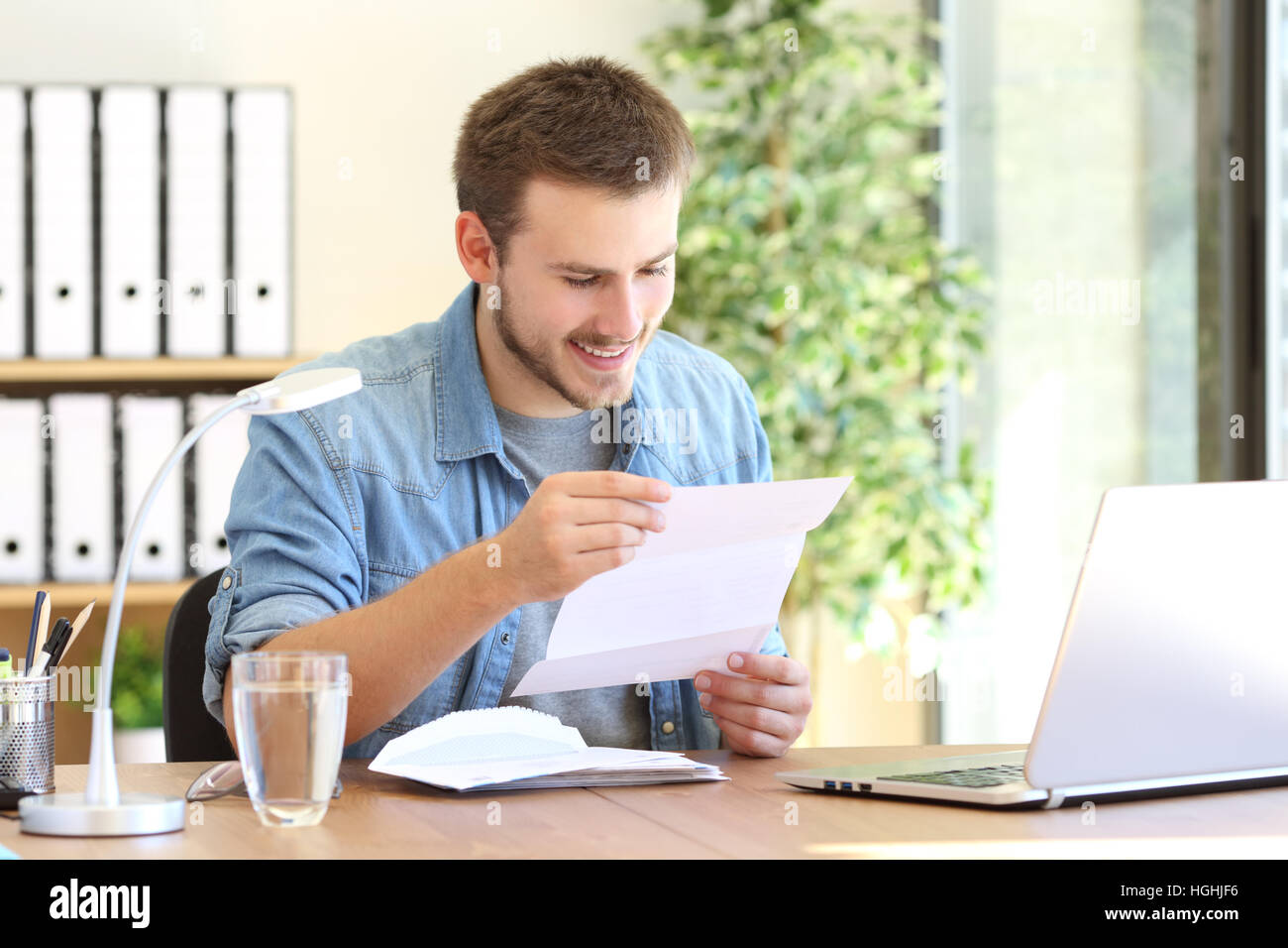 Happy entrepreneur working reading a letter in a desk at office - Stock Image