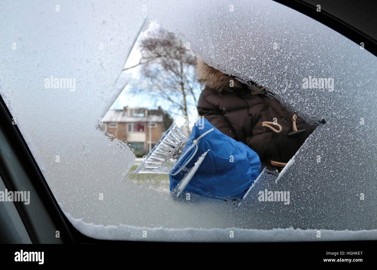 Woman removing ice and snow from a car window with a ice scraper - Stock Image