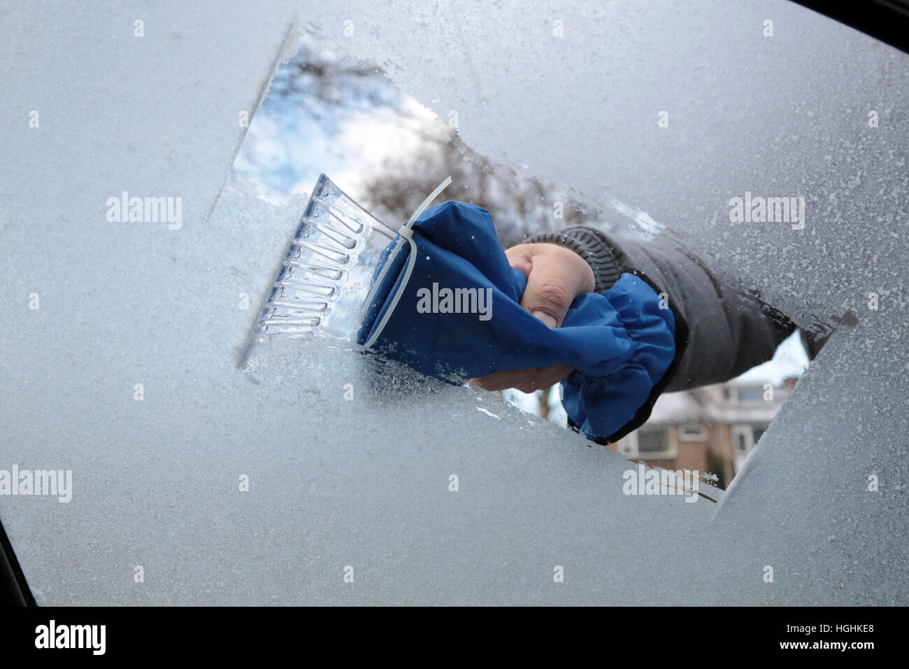 Man removing ice and snow from a car window with a ice scraper - Stock Image