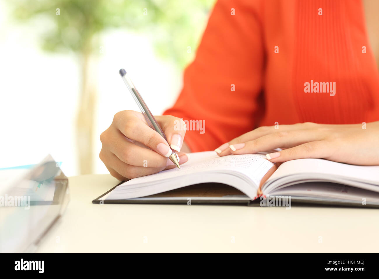 Businesswoman hand writing in agenda on a desk in the office - Stock Image