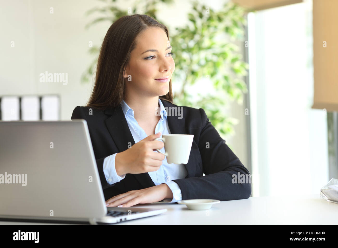 Pensive executive relaxing in a desk at office looking through the window with a cup of coffee - Stock Image