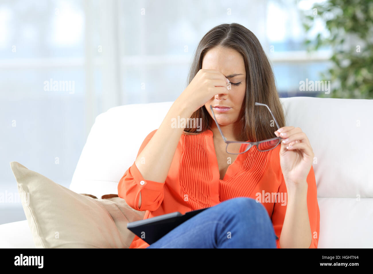 Woman with glasses suffering eyestrain after reading an ebook sitting on a couch at home - Stock Image