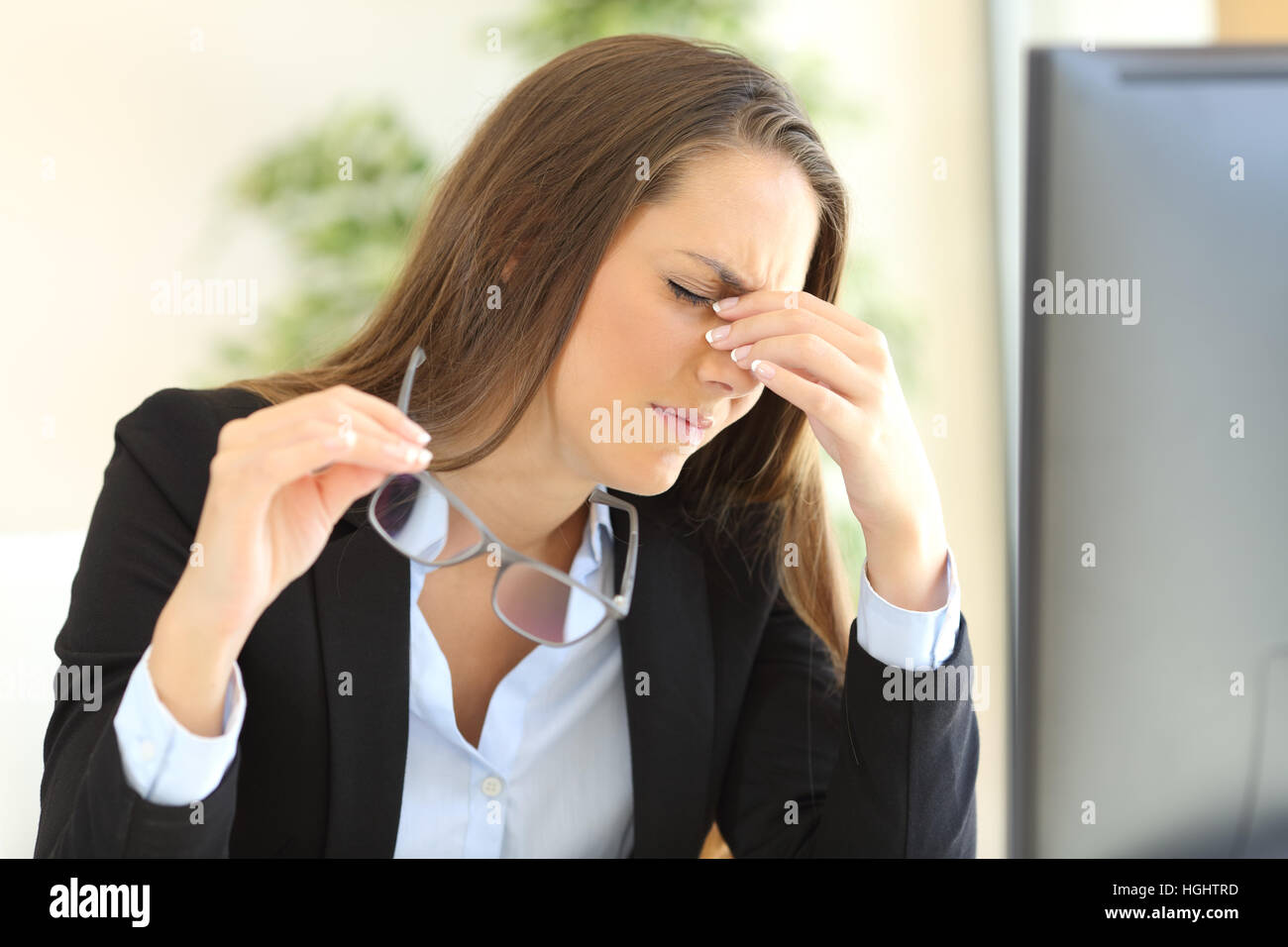 Fatigued businesswoman holding glasses suffering eyestrain in front of a pc screen at office - Stock Image
