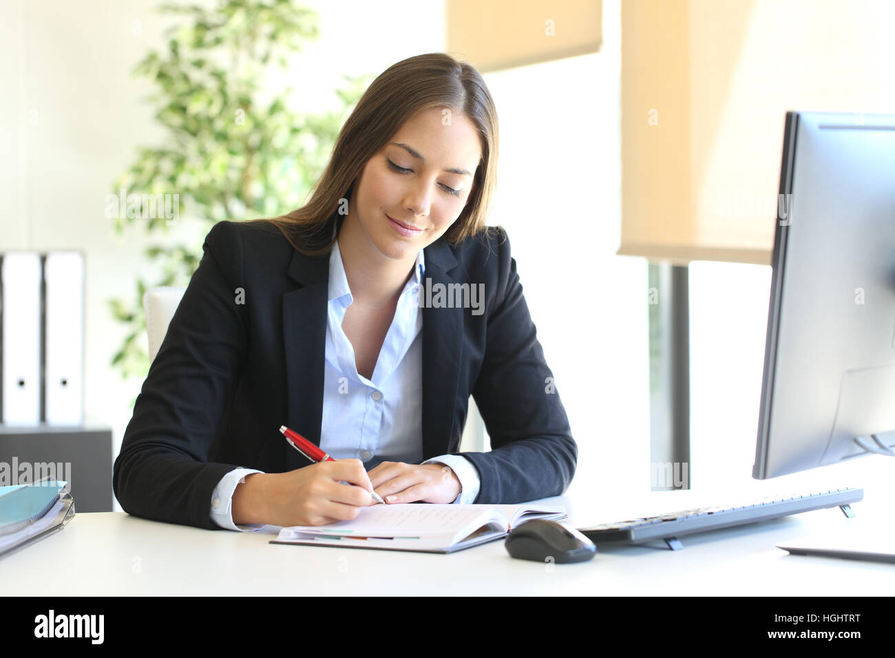 Busy businesswoman writing in an agenda on a desktop at office - Stock Image