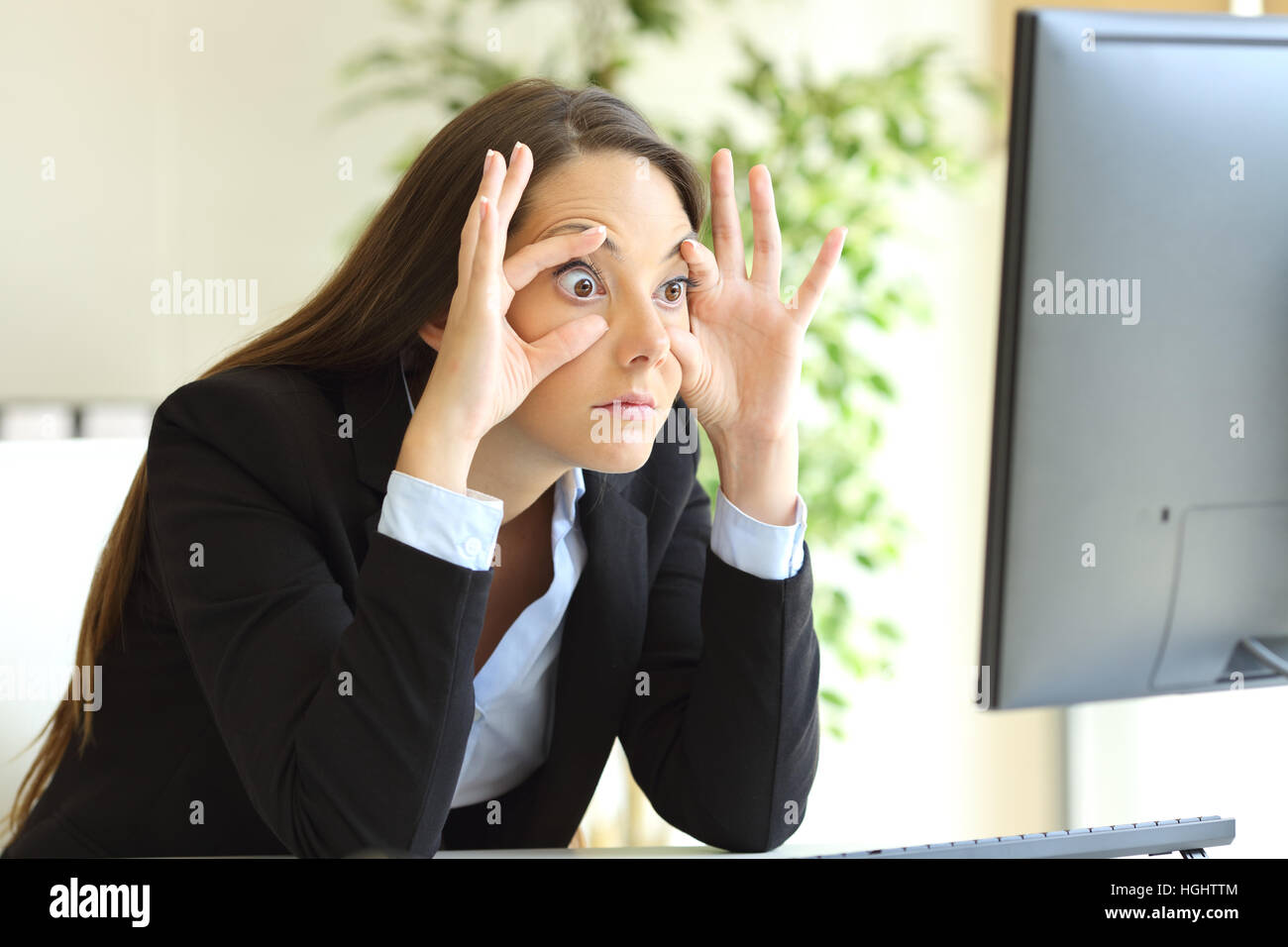 Sleepy businesswoman trying to stay awake keeping the eyes opened with the fingers watching a desktop computer monitor - Stock Image