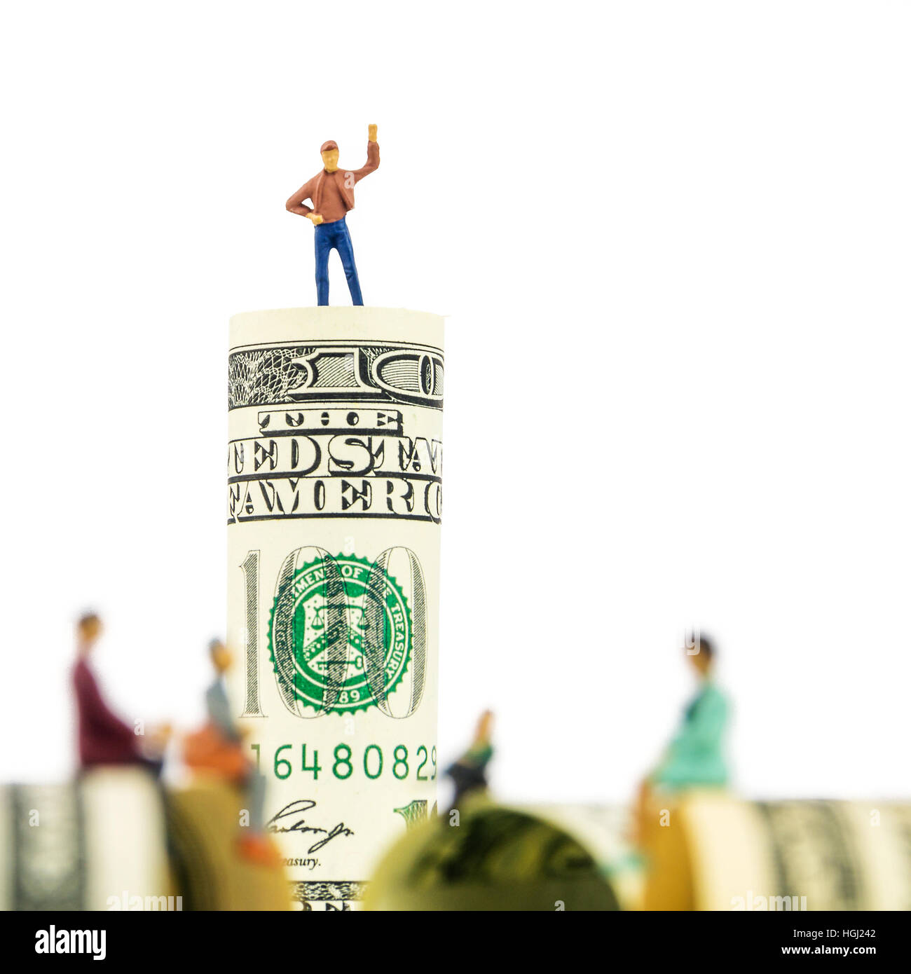 defocused miniature figurines sitting on the edge of 100 dollar banknote with a man standing on dollar bill at the - Stock Image