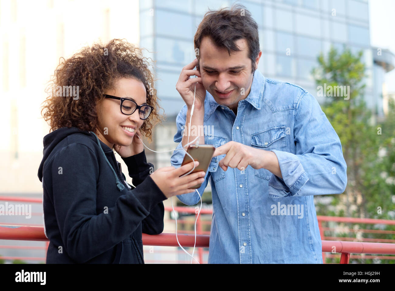 Two friends using mobile phone and listening to music in the street - Stock Image