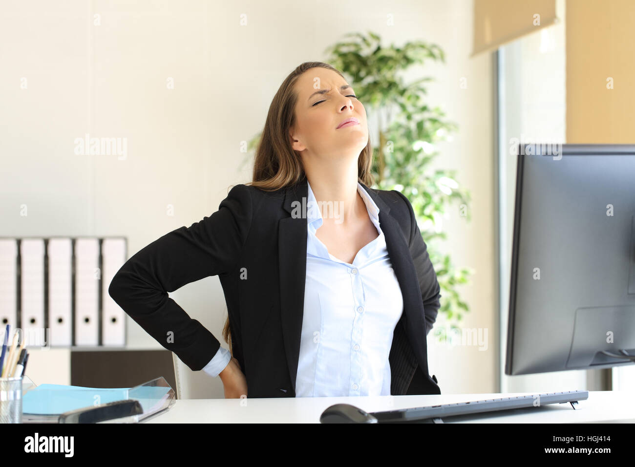 Unhappy businesswoman suffering back ache sitting on an uncomfortable seat at work indoors in her office - Stock Image