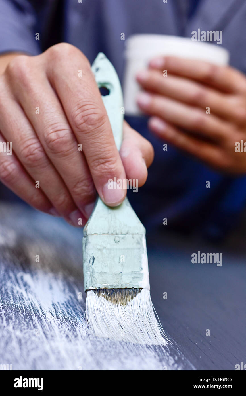closeup of a young caucasian man in a working coat applying a white chalk effect paint to a gray wooden board with - Stock Image