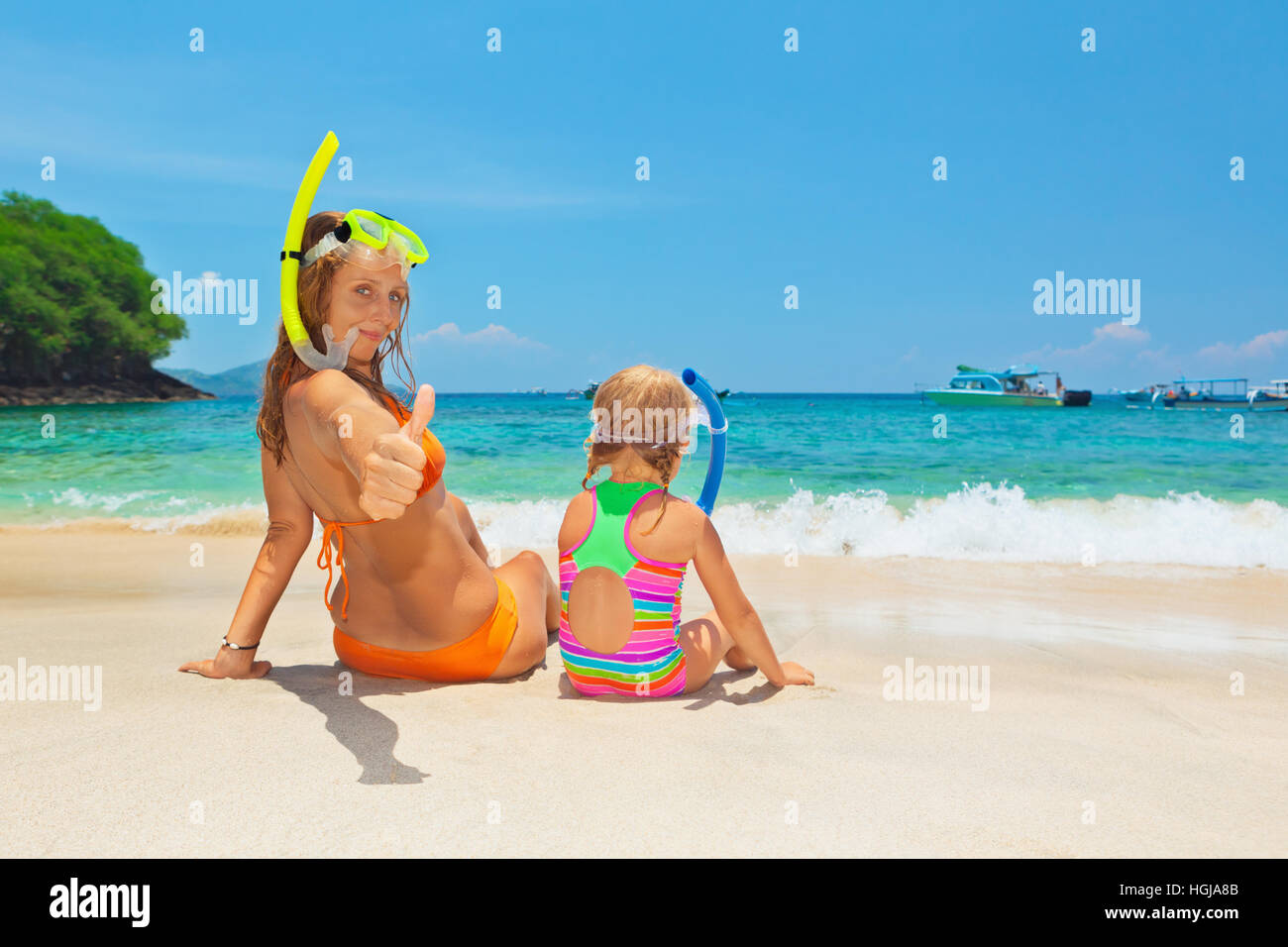 Happy family - mother with baby girl have fun in beach pool with sea surf. Travel  lifestyle, people water sport - Stock Image