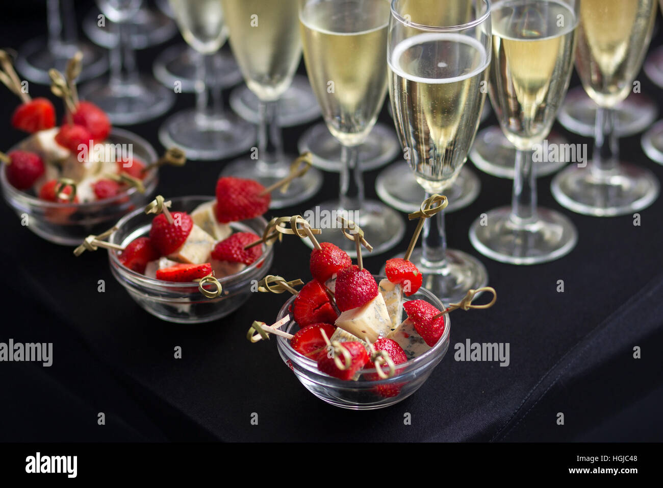 Canapes of cheese and strawberries with champagne - Stock Image