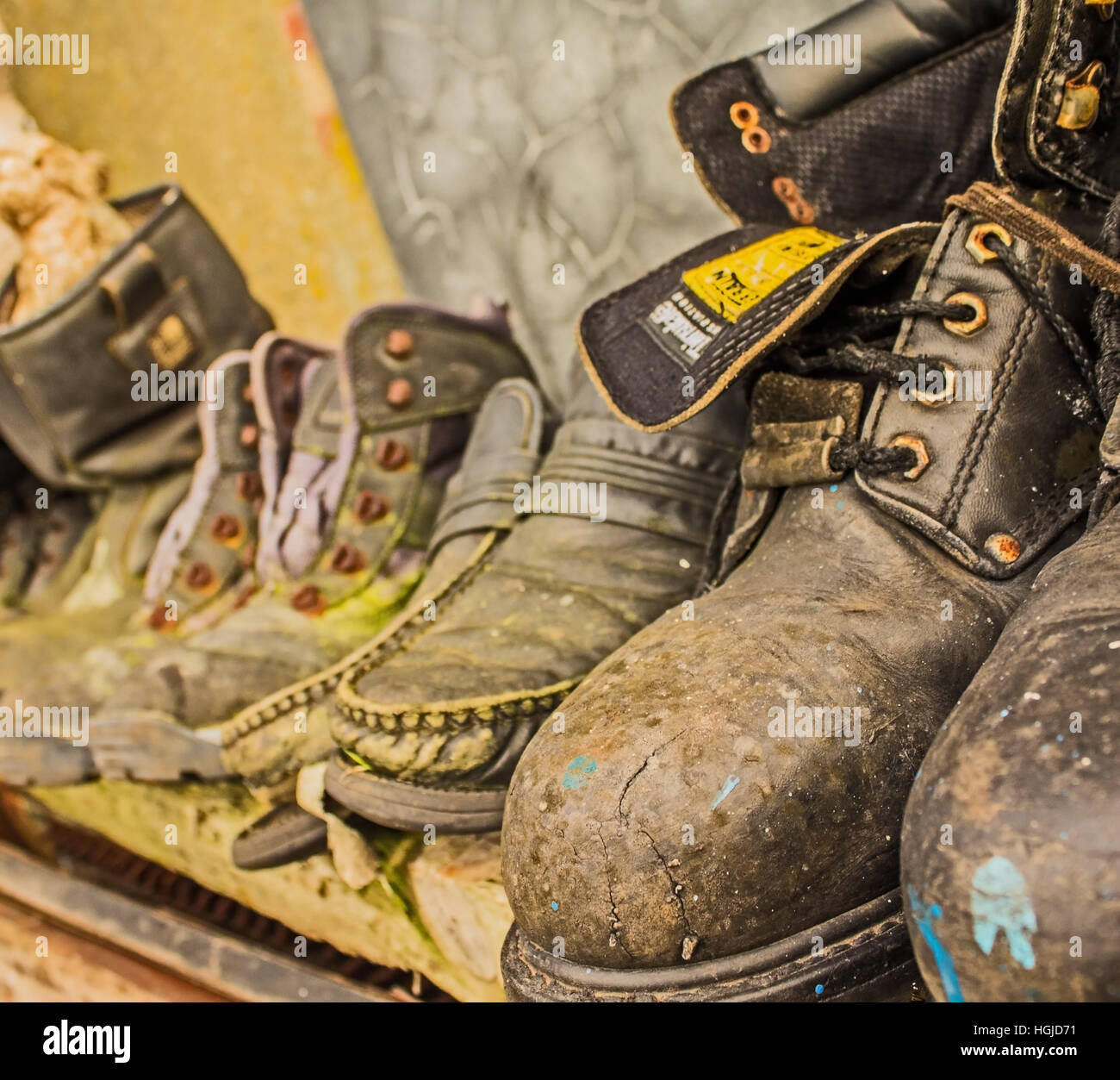 old boots and shoes on a shelf - Stock Image