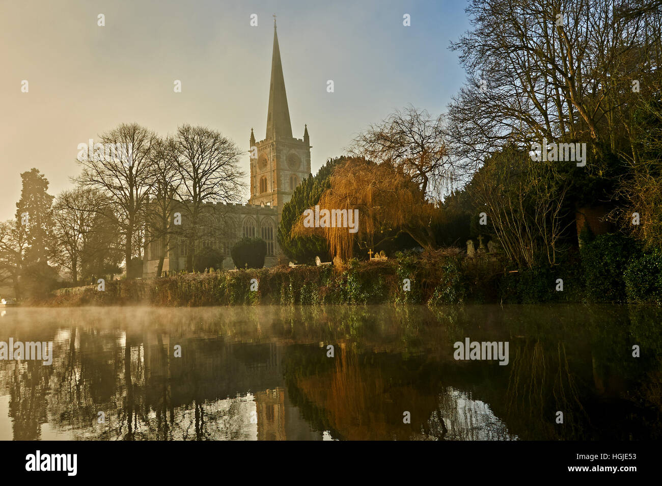 Holy Trinity church Stratford upon Avon stands overlooking the River Avon on a misty winter morning. - Stock Image