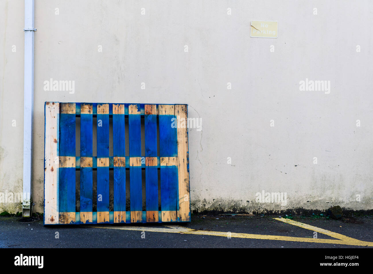 Blue wooden pallet leaning against a white concrete wall with copy space. - Stock Image