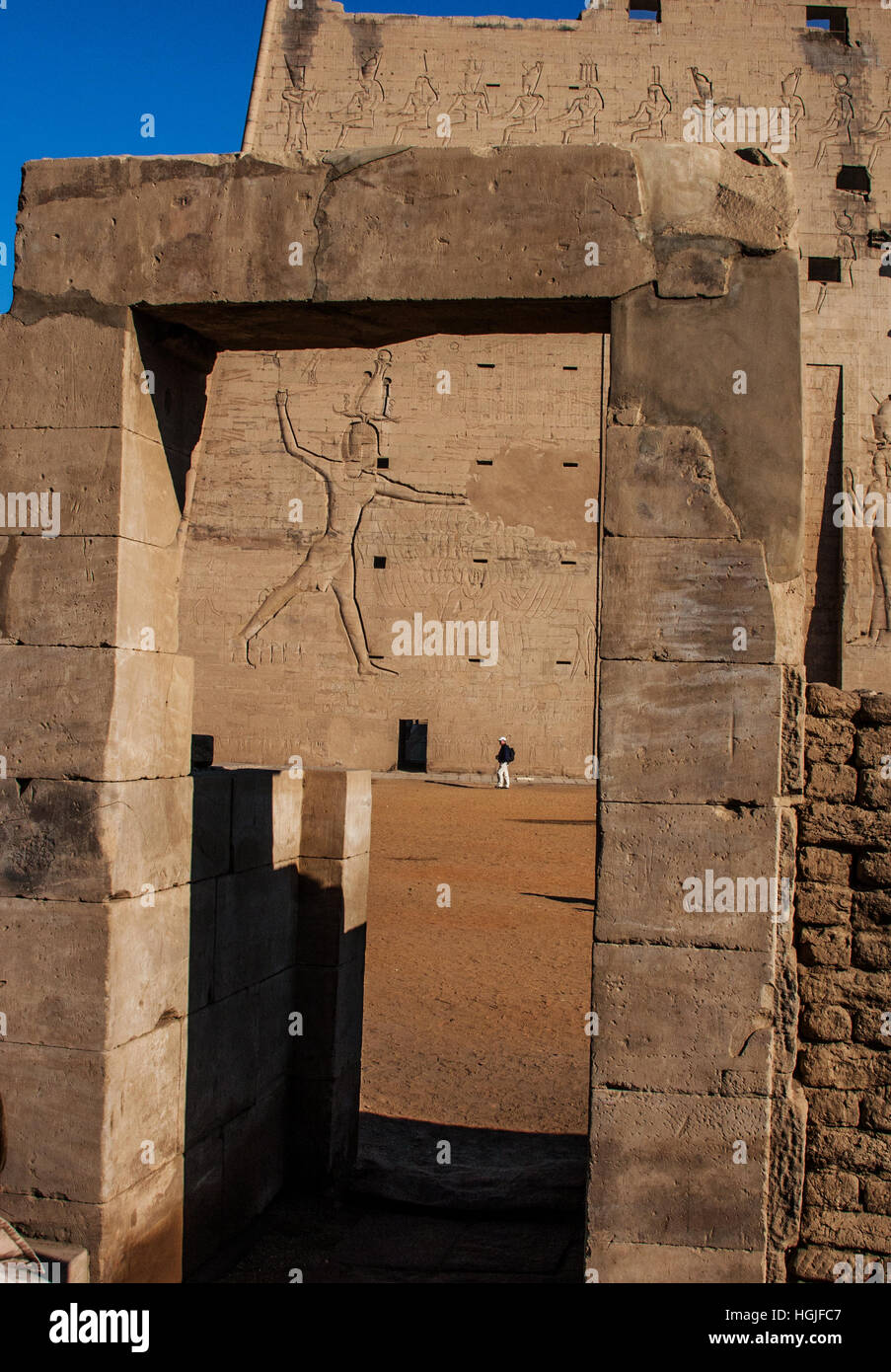 Man, dwarfed by the size of the Temple of Edfu on the Nile in Egypt, heads to a tiny side entrance as seen through Stock Photo